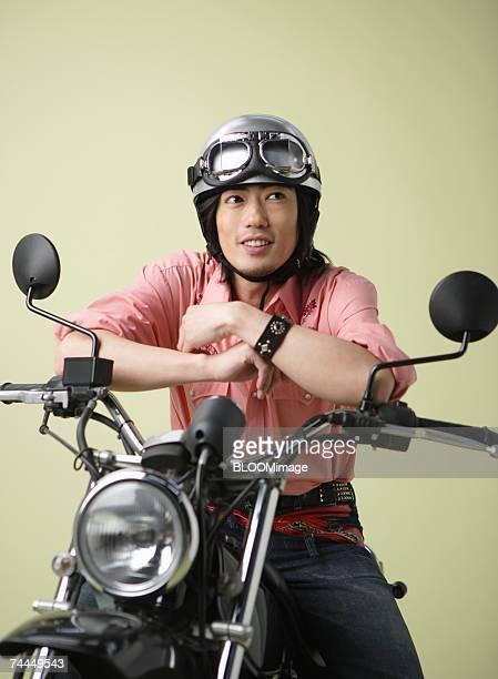 Japanese man smiling with sitting on seat of motorbike