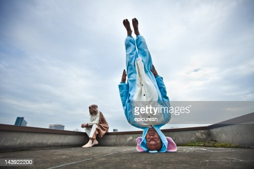 Japanese man standing on his head in elephant costume : Stock Photo