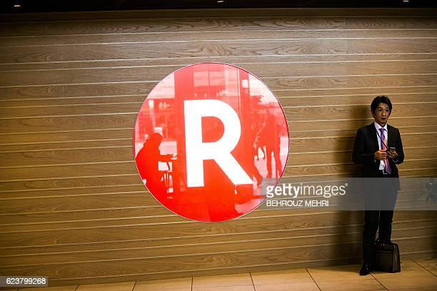 A Japanese man stands next to the logo of Japan's electronic commerce and internet firm Rakuten at the company headquarters in Tokyo on November 17...