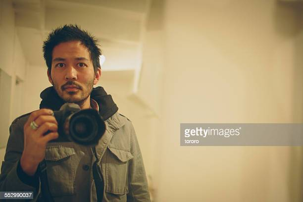 Japanese man taking a photo of himself in mirror