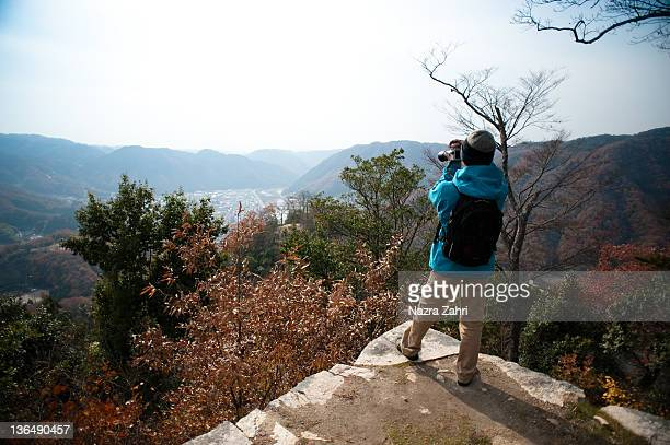 Japanese man taking photo of autumn