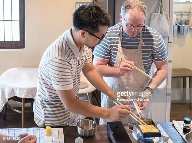 Japanese Man Teaching Caucasian Man How to Cook Tamagoyaki Omelette