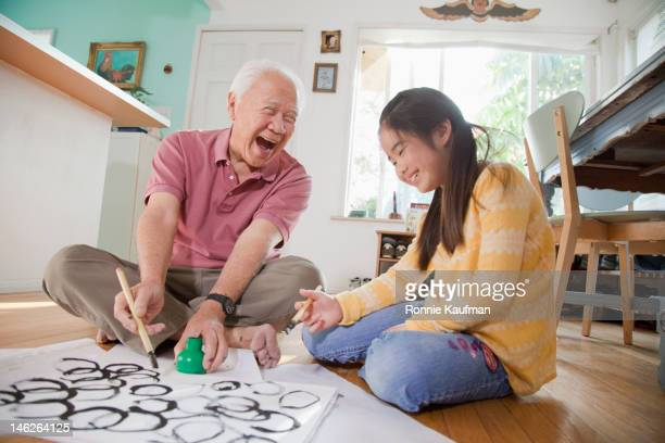 Japanese man teaching granddaughter calligraphy