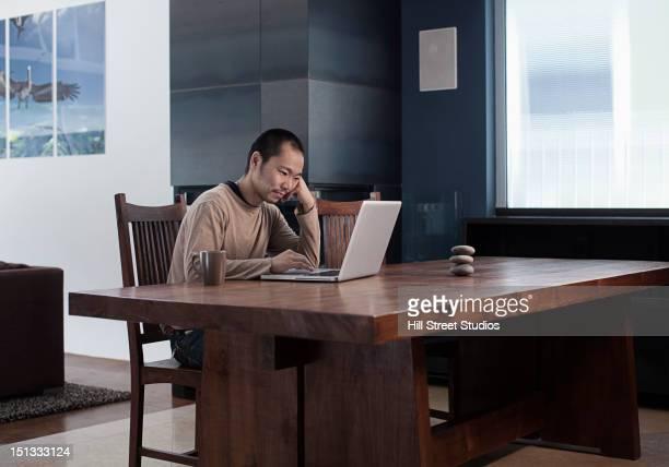 Japanese man using laptop at table