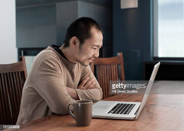Japanese man using laptop at table