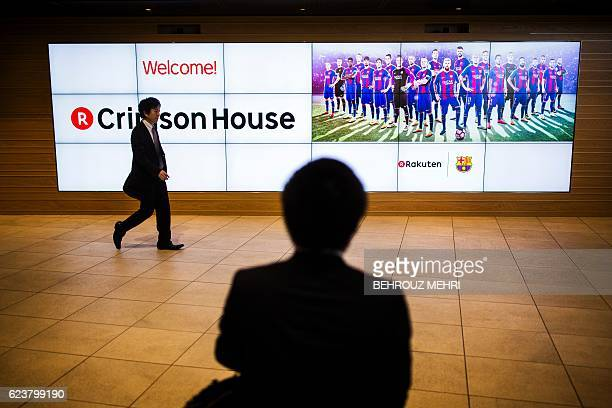 A Japanese man walks past a picture of Spanish FC Barcelona football team players with logos of the team and Japan's electronic commerce and internet...