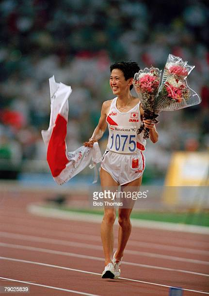 Japanese marathon runner Yuko Arimori holds her national flag along with bouquets of flowers in celebration after crossing the finish line in second...