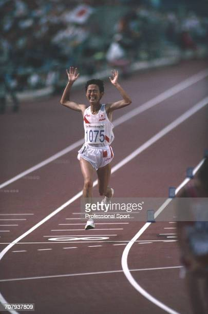 Japanese marathon runner Yuko Arimori raises her arms in the air in celebration as she crosses the finish line in second place to win the silver...