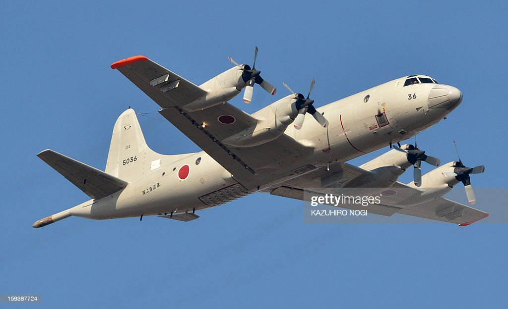 A Japanese Maritime Self Defense Force P3-C four-engine turboprop maritime surveillance aircraft flies over Self Defense troops taking part in a new year military drill at the training grounds at Narashino, suburban Tokyo on January 13, 2013. A total of 300 personnel, 20 aircraft and 33 vehicles took part in the open exercise at the defense force's Narashino training ground.