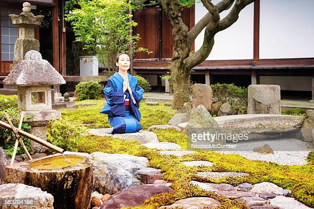 Japanese mature female in blue kimono meditates at temple garden