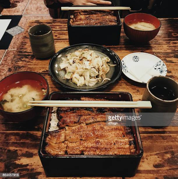 Japanese meal for two person with grilled eel served on rice in box with miso soup and fried mixed vegetables