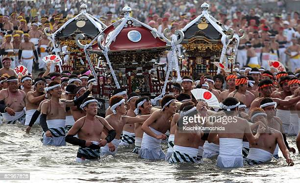 Japanese men carry portable shrines into the sea during the Ohara Hadaka Festival on September 23 2008 in Isumi City Chiba Prefecture Japan The Ohara...
