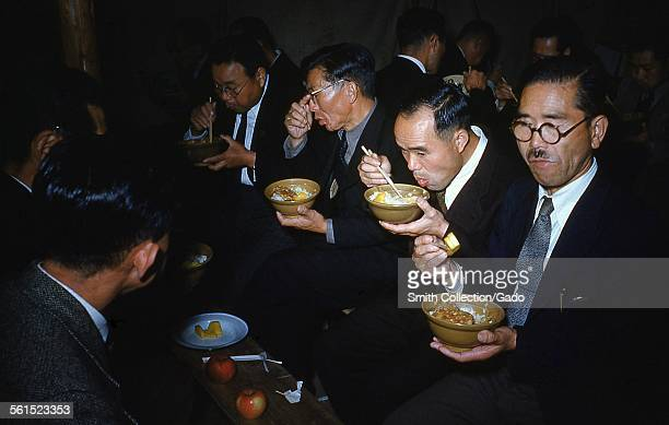 Japanese men eating ramen rice and eggs with chopsticks dressed in formal suits wearing glasses with apples and other food on a table in a crowded...