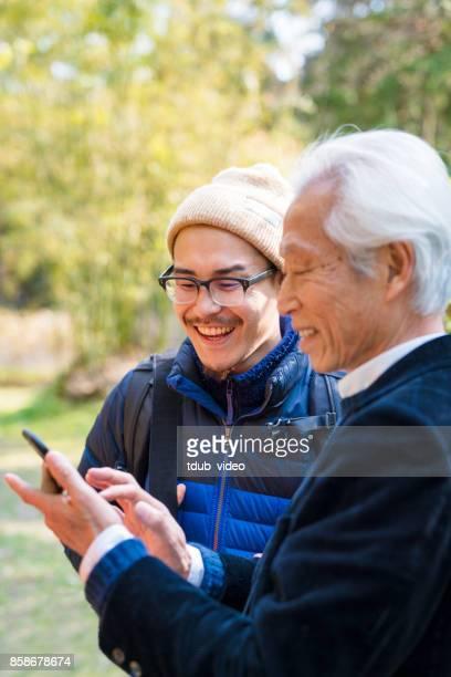 Japanese men laughing looking at phone