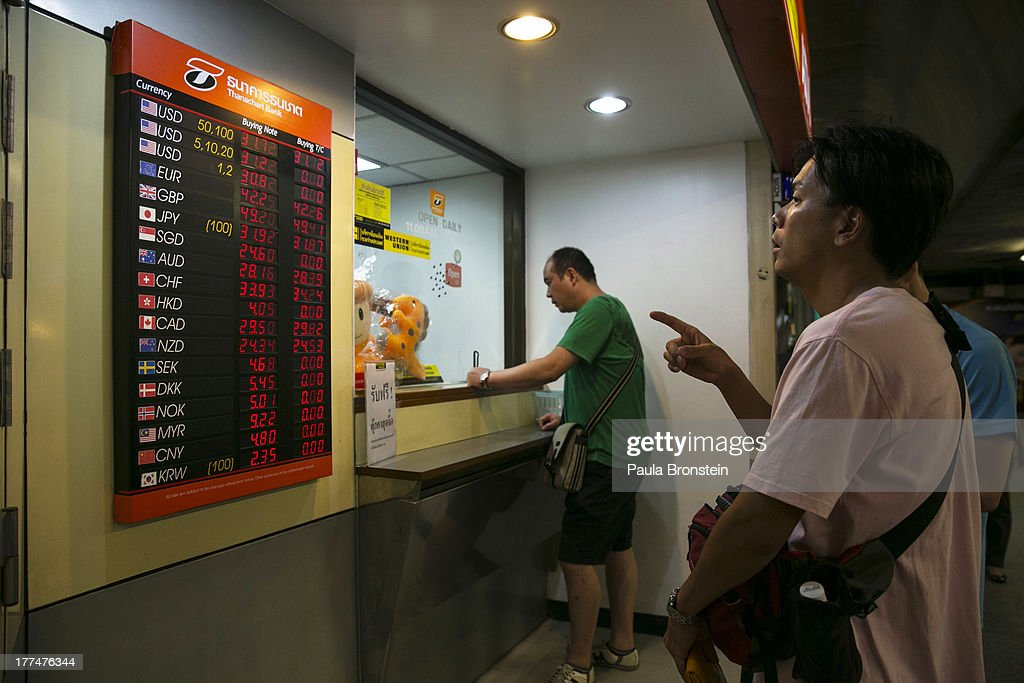 Japanese men looks at the currency board at a money exchange bank kiosk on August 23, 2013 in downtown Bangkok, Thailand. The local currency dropped to its lowest level since August 2010. Against the US dollar the Thai baht fell to 32.09/32.13 dropping about 5% this year.