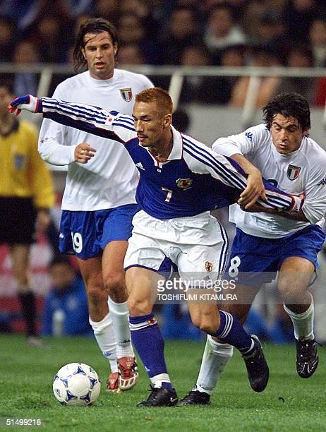 Japanese midfielder Hidetoshi Nakata is pulled by Italian midfielder Gennaro Ivan Gattuso during the second half of the friendship match against...