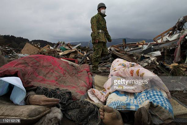 Japanese military walk by a body lying in the rubble of a village destroyed by the devastating earthquake and tsunami on March 15 2011 in...