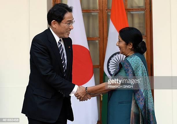 Japanese Minister of Foreign Affairs Fumio Kishida shakes hands with Indian Foreign Minister Sushma Swaraj prior to a meeting in New Delhi on January...