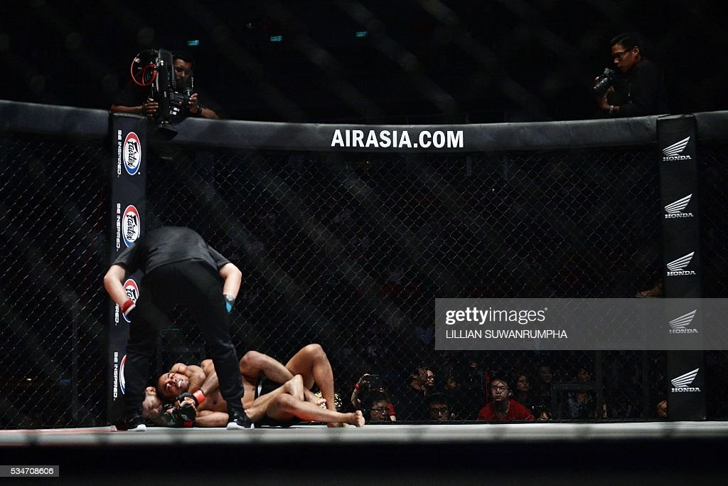 Japanese MMA fighter Yoshitaka Naito attempts to lock in a choke on Thai fighter Dejdamrong Sor Amnuaysirichoke during the first ever ONE FC event in Bangkok on May 27, 2016. / AFP / LILLIAN