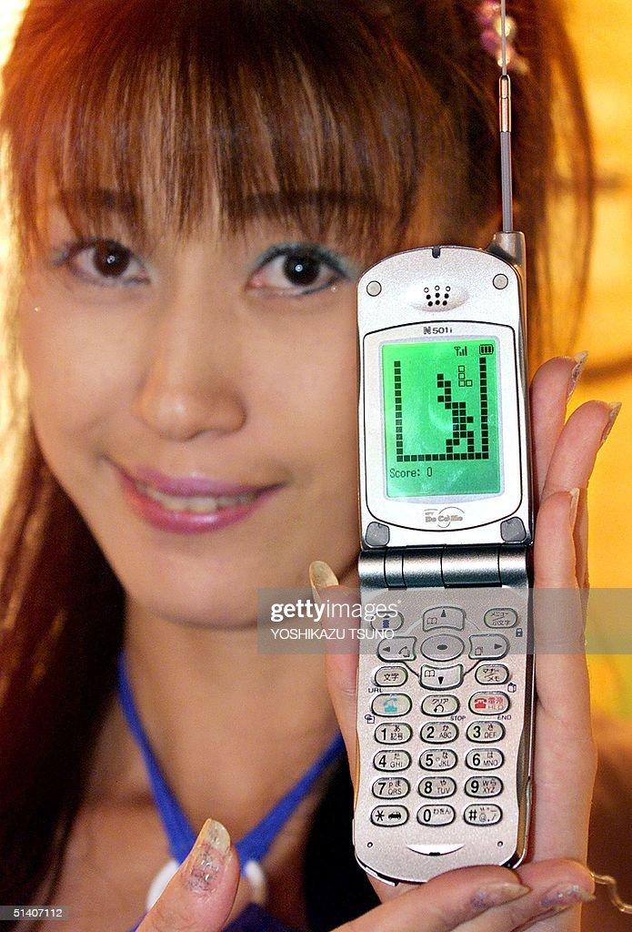 Japanese mobile communication giant NTT Docomo employee Yoshie Iijima displays a 'Tetris' game on a protype model of Docomo's mobile phone which has...