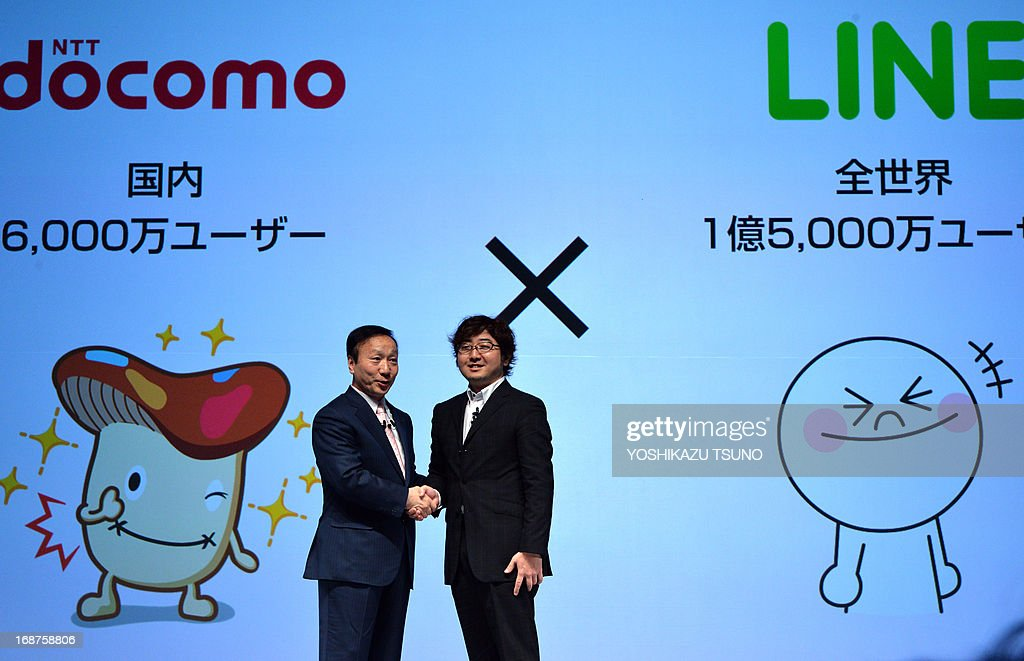 Japanese mobile communication giant NTT Docomo president Kaoru Kato (L) shakes hands with Akira Morikawa, president of Line, a smartphone based social networking service (SNS) in Tokyo on May 15, 2013. NTT Docomo also announced the company had formed a business alliance with smartphone based free voice and messaging service provider Line to enhance the convenience of voice and messaging applications for Docomo's smartphones. AFP PHOTO / Yoshikazu TSUNO