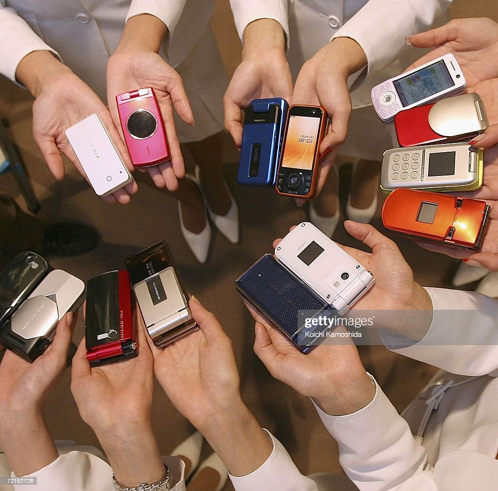 Japanese Models display mobile communication giant NTT DoCoMo's new mobile 14 new 3G FOMA handsets the 903i series during a press preview on October...