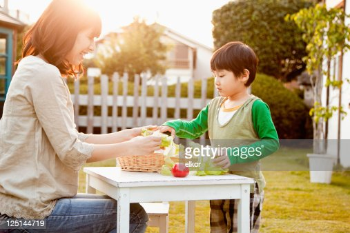 Japanese mom and son with organic vegetables in the garden. : Stock Photo