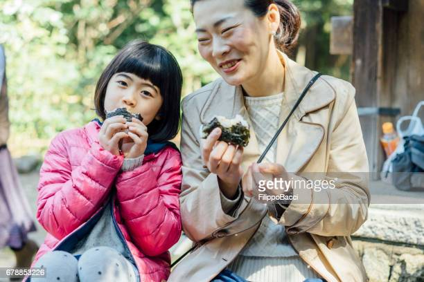 Japanese mother and daughter eating onigiri together