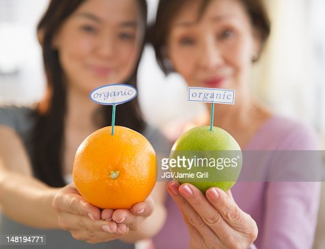 Japanese mother and daughter holding fruit with organic label : Stock Photo