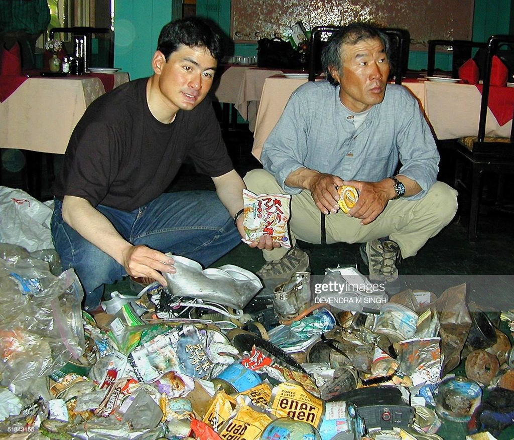Japanese mountaineer and leader of the Noguchi-Asia Group Everest Cleaning Expedition 2001, Ken Noguchi (L) and South Korean member Lee Sang-Bae (R) display the garbage collected from Mt. Everest, in Kathmandu, 25 May 2001. Their expedition collected some 1,600 kilos of garbage used by different mountaineers on world's tallest mountain. Leader Nogochi plans an exhibition of the garbage in Japan, South Korea and China for campaigning for environmental awareness. AFP PHOTO/Devendra M. SINGH
