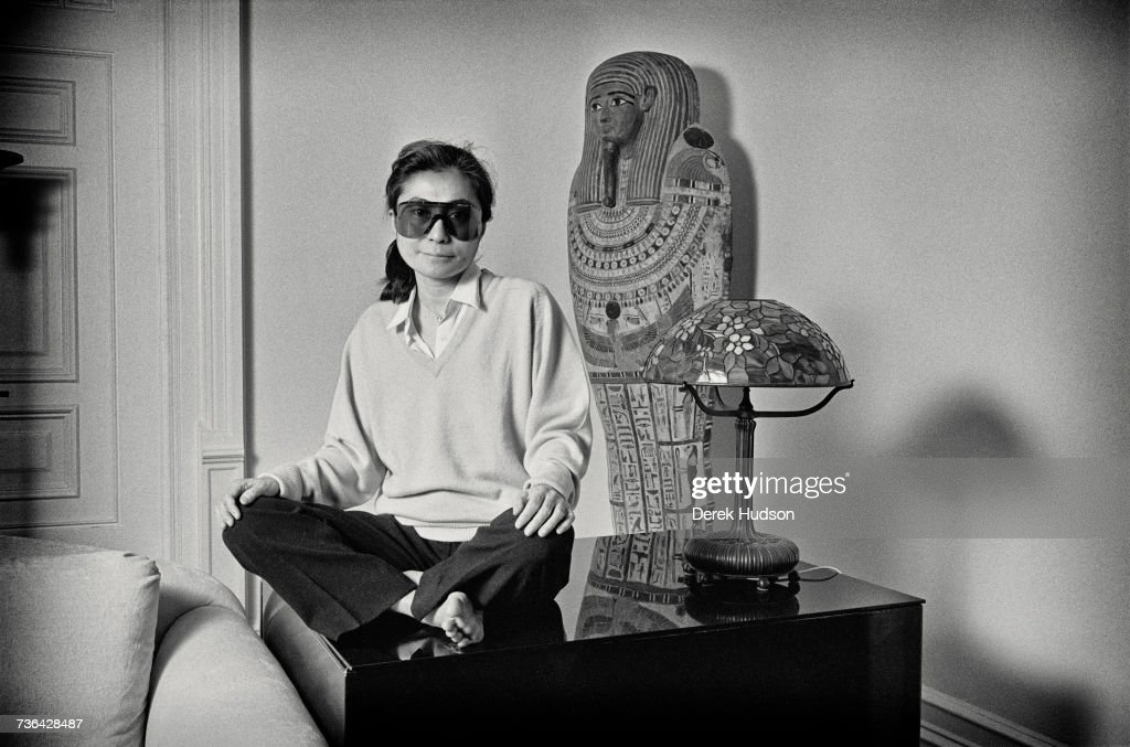 Japanese multimedia artist, singer and songwriter Yoko Ono in the lounge of the apartment she shared with John Lennon, one year to the day after he was murdered outside the Dakota building where they lived on Central Park West, Manhattan, December 8th 1981. She is wearing a pair of Porsche wrap around sunglasses.