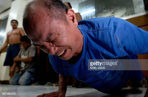 A Japanese national is detained for drinking in a public place in Las Pinas south of Manila do 40 pushups during the police's operation called 'Oplan...