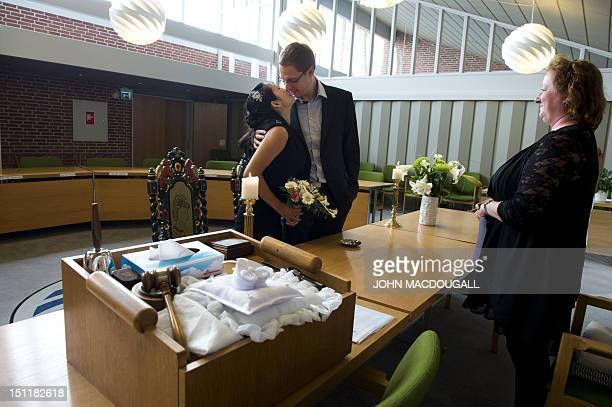 Japanese national Natsuko Kubota and German national Benjamin Krause kiss as Danish registrar Joan Lykke Ammersboell looks on during a wedding...
