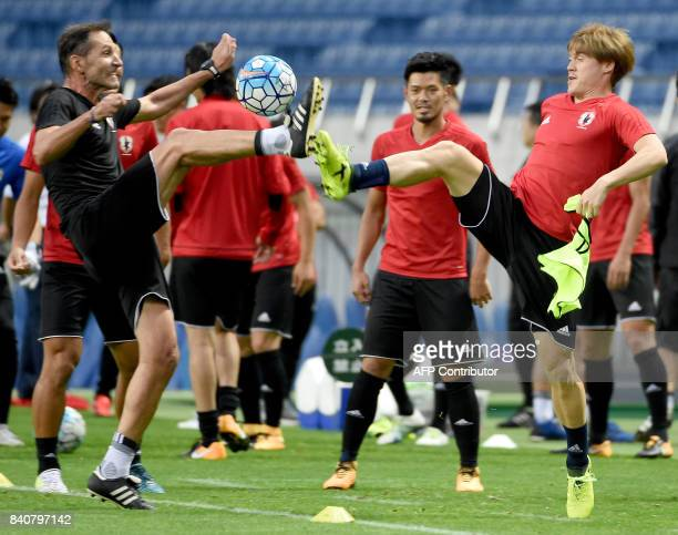 Japanese national team defender Gotoku Sakai battles for a ball with a coach during the training session at Saitama Stadium in Saitama on August 30...