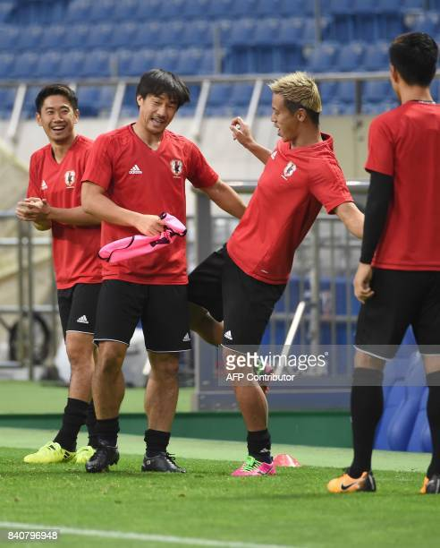 Japanese national team forward Keisuke Honda jokes with Shinji Okazaki beside midfielder Shinji Kagawa during the training session at Saitama Stadium...