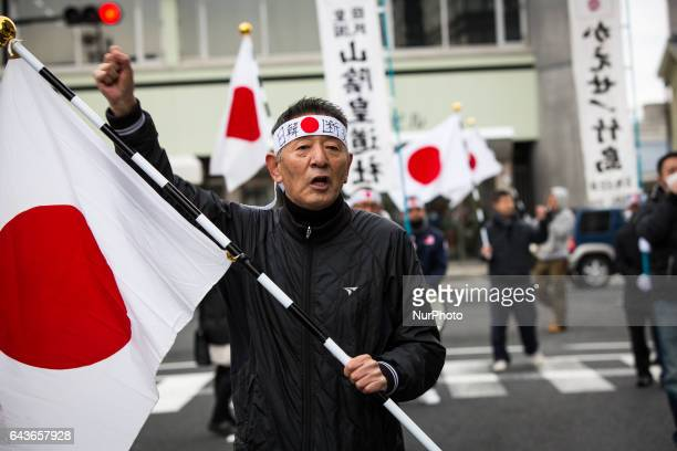 Japanese nationalists march with banners and flags to protest South Korea to return disputed islets prior to the ceremony of Takeshima Day a small...