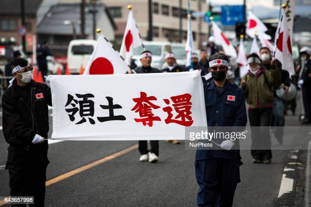 Japanese nationalists march with flags to protest South Korea to return disputed islets prior to the Takeshima Sovereignty Ceremony a small disputed...