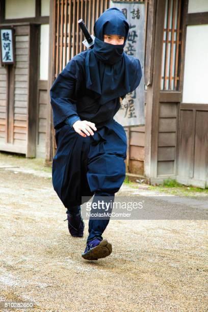 Japanischer Ninja im schwarzen Kostüm läuft schnell in alten Edo-Dorf