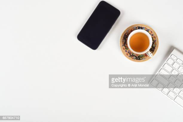 Japanese office desk top view with mobile phone, tea cup plate, tea pot, computer keyboard, white copy space
