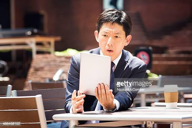 日本の会社員的なニュースを読むタブレット屋外
