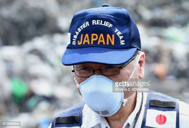 A Japanese official with a disaster relief team surveys the site of a garbage dump collapse that killed 32 people on the northeastern edge of Sri...