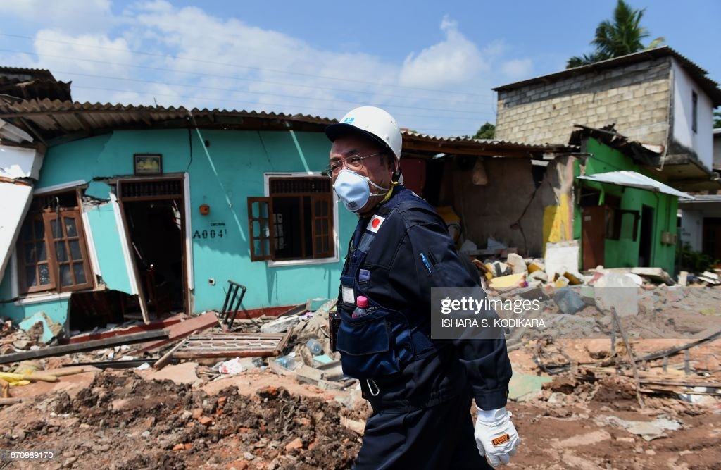 Japanese official with a disaster relief team surveys the site of a garbage dump collapse that killed 32 people on the northeastern edge of Sri Lankas capital Colombo on April 21, 2017. A Japanese disaster relief team is advising the Sri Lankan government on measures to deal with the huge rubbish dump and relocate hundreds of families in the neighbourhood following the disaster. / AFP PHOTO / Ishara S. KODIKARA