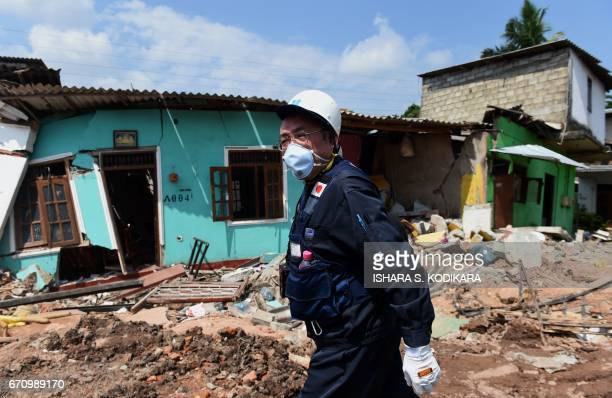 Japanese official with a disaster relief team surveys the site of a garbage dump collapse that killed 32 people on the northeastern edge of Sri...