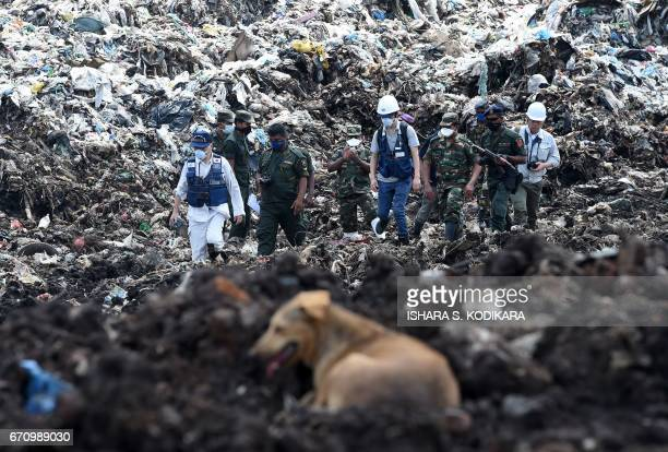 Japanese officials with a disaster relief team survey the site of a garbage dump collapse that killed 32 people on the northeastern edge of Sri...