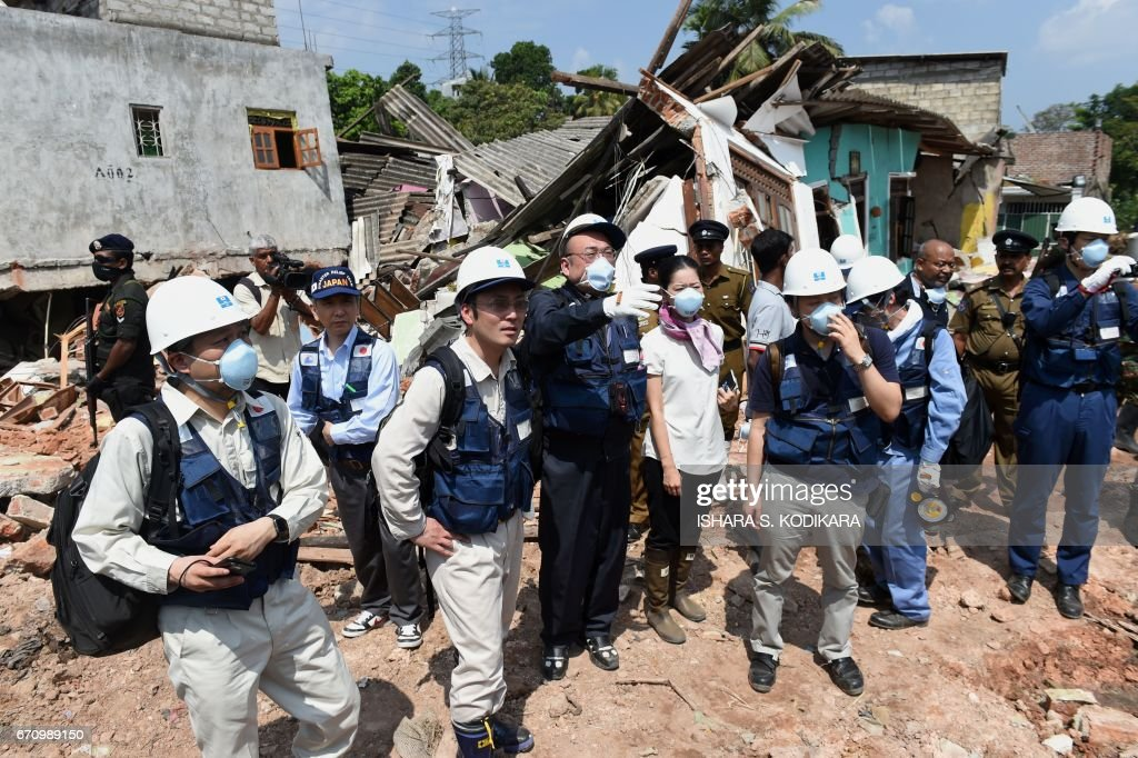 Japanese officials with a disaster relief team survey the site of a garbage dump collapse that killed 32 people on the northeastern edge of Sri Lankas capital Colombo on April 21, 2017. A Japanese disaster relief team is advising the Sri Lankan government on measures to deal with the huge rubbish dump and relocate hundreds of families in the neighbourhood following the April 14 disaster. / AFP PHOTO / Ishara S. KODIKARA