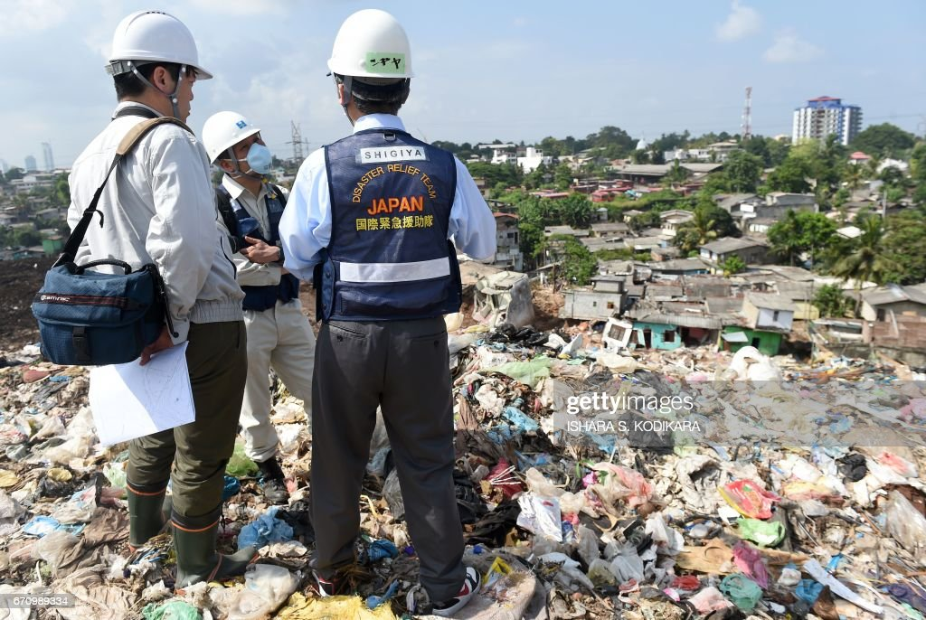 Japanese officials with a disaster relief team survey the site of a garbage dump collapse that killed 32 people on the northeastern edge of Sri Lankas capital Colombo on April 21, 2017. A Japanese disaster relief team is advising the Sri Lankan government on measures to deal with the huge rubbish dump and relocate hundreds of families in the neighbourhood following the disaster. / AFP PHOTO / Ishara S. KODIKARA