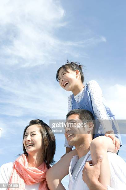 Japanese parents and girl smiling and looking away