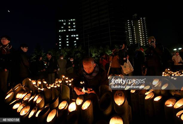 Japanese people light up a bamboo lanterns to pray for the victims of the Great Hanshin Earthquake marking the 20th anniversary on January 17 2015 in...