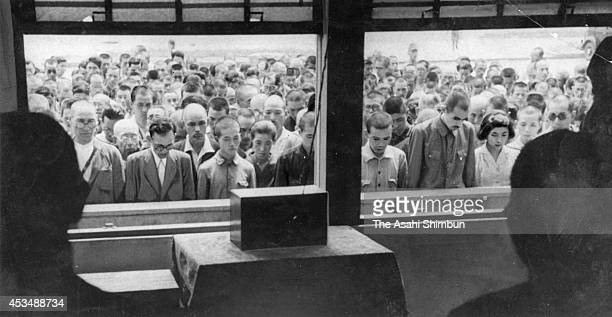 Japanese people listen to the 'Gyokuon Hoso' which is the radio broadcast of the Emperor Hirohito reading the Imperial Rescript of acceptance of the...