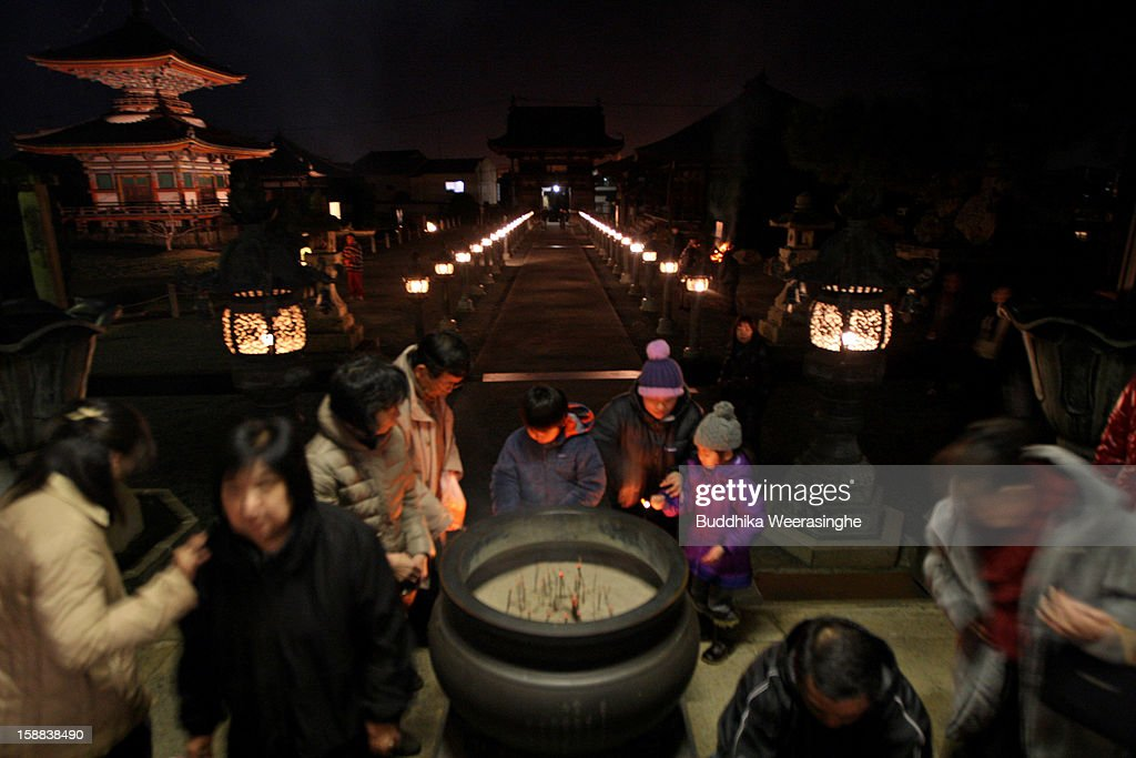 Japanese people offer incense sticks as they see in the New Y at the Sagami-ji Buddhist temple on January 1, 2013 in Kasai, Japan. Japanese people attend the Buddhist temple at midnight on December 31 for the ringing of the temple bell to welcome in the New Year or 'Omisoka' as it is known in Japan. In Japanese belief there are 108 elements to the human mind, so the bell is rung 108 times as a blessing of happiness for the New Year.